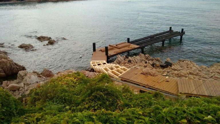 delle assi di legno assemblate su delle rocce, accanto degli attrezzi e dietro vista del verde