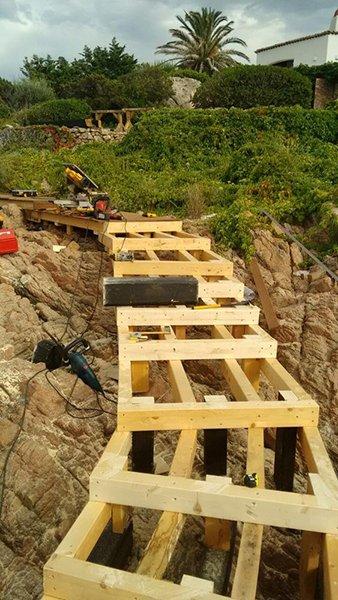 vista in lontananza del verde,le rocce e il ponticello in costruzione vicino al mare