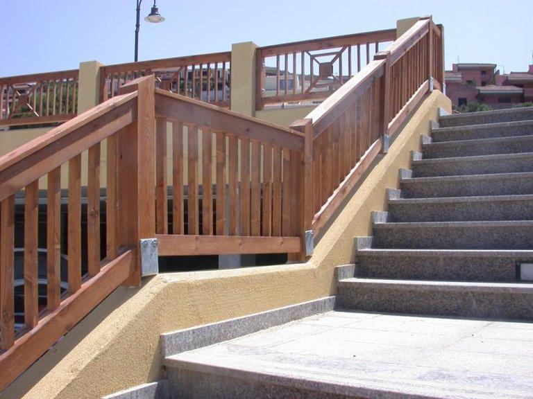 una scalinata in granito con vista del corrimano in legno