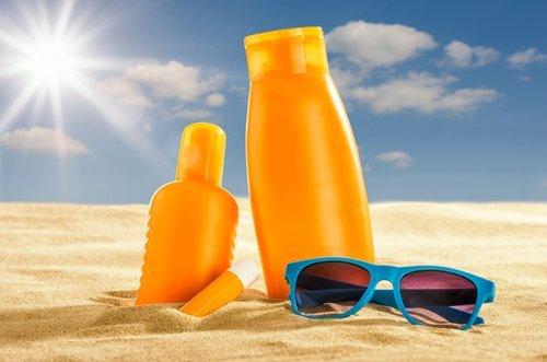 prodotti solari su una spiaggia accanto ad occhiali da sole