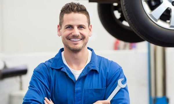 man-in-blue-smiling-holding-tool