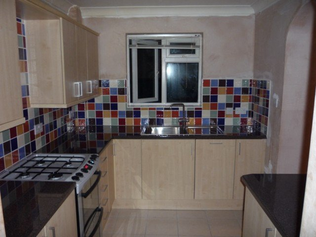 coloured tiles and black worktop