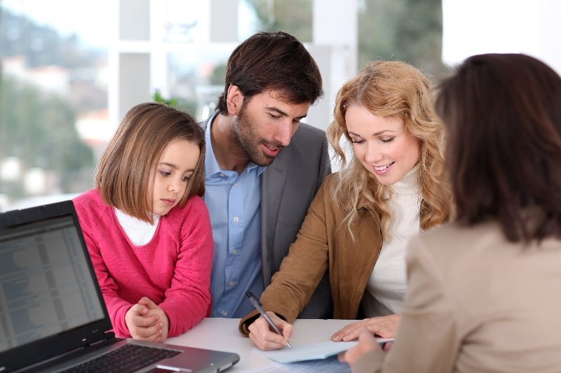 Woman signing paperwork with family beside her