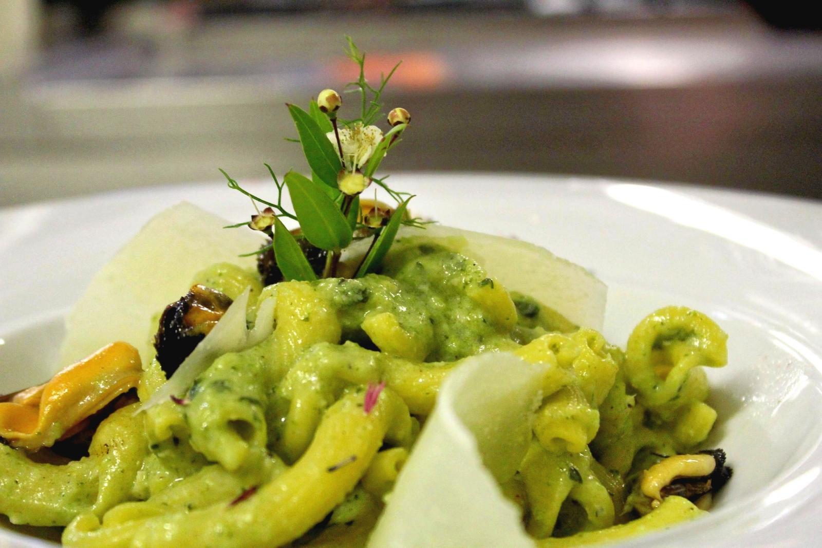 un piatto di pasta con salsa verde e delle cozze