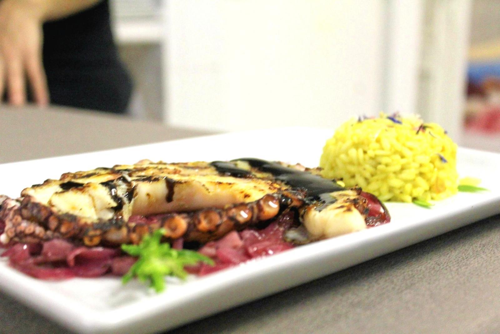 un piatto a base polipo grigliato e accanto del riso giallo
