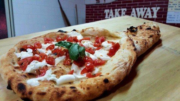 una pizza con pomodori e fette di mozzarella