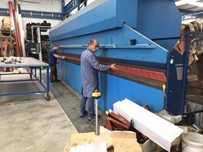 operaio in officina sistema una macchina per lavorazioni serramenti