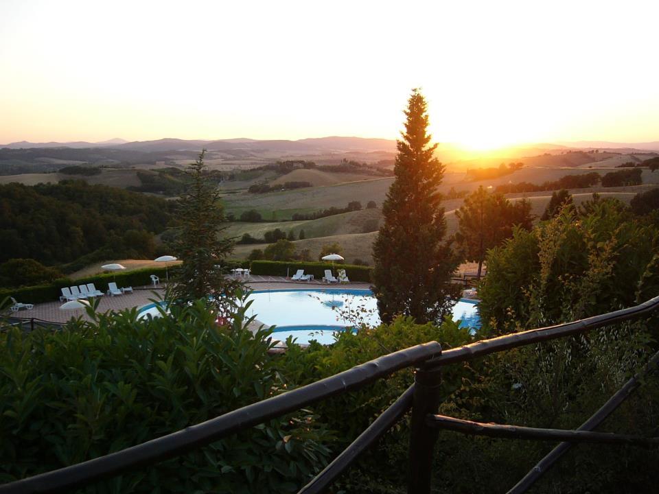 una piscina e accanto degli sdraio con vista delle colline