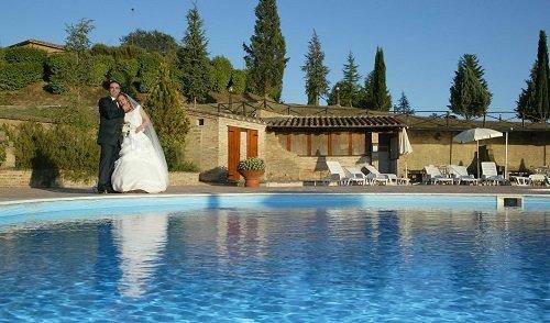 due sposi abbracciati accanto a una piscina