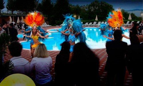 delle persone sedute attorno a una piscina e delle ragazze in costume da carnevale che ballano