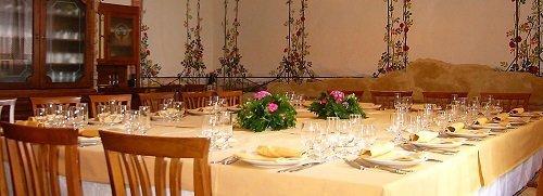 un tavolo apparecchiato e  due composizioni di fiori al centro