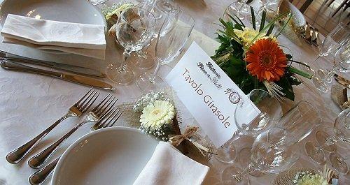 un tavolo apparecchiato e un'etichetta con scritto Tavolo Girasole