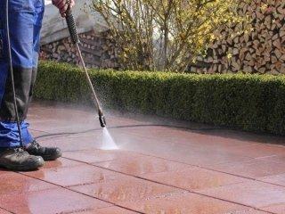 una persona che pulisce una superficie con un idropulitrice