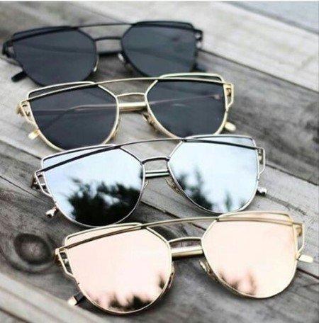 quattro paia di occhiali da sole di diversi tipi,  due con vetri scuri, due con vetri a specchio
