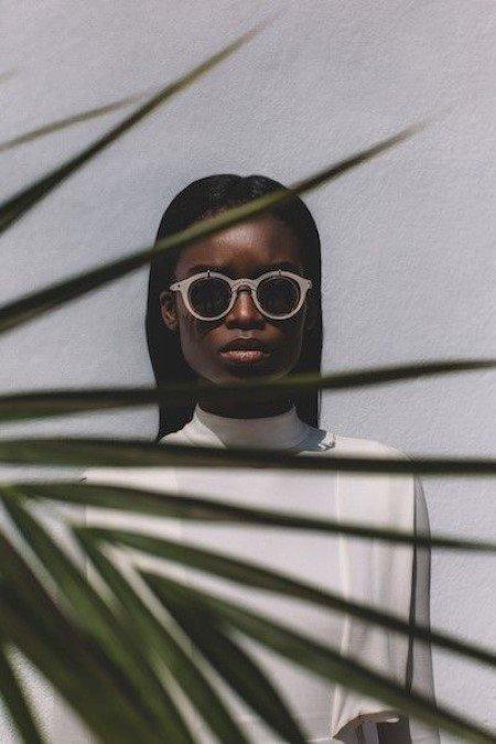 foto modella di colore, con occhiali da sole color pastello