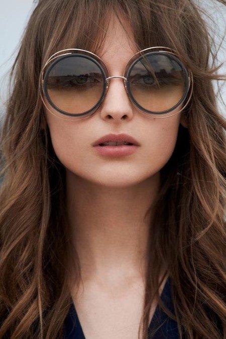 volto di una donna con capelli castani e frangetta che indossa occhiali da sole