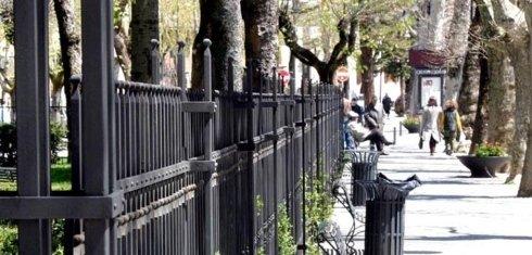 una ringhiera e delle persone che camminano in un viale