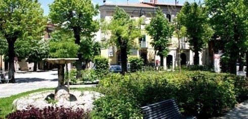 una fontana, dei cespugli,una panchina e degli alberi