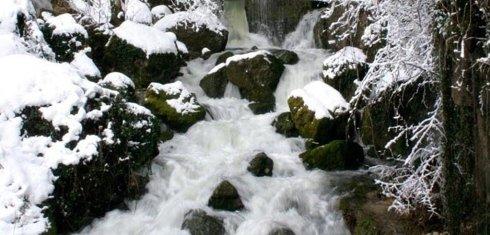 un fiume che scorre tra le rocce e della neve