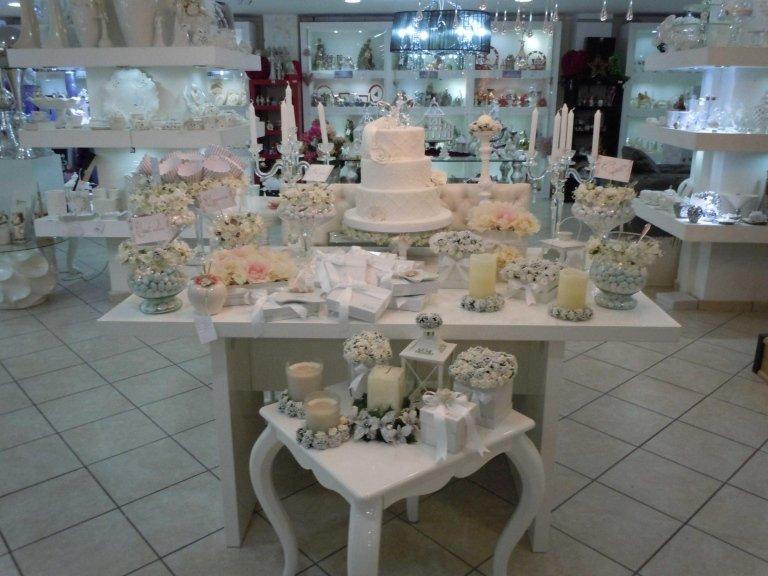 tavolo e scaffale con bomboniere e oggetti da casa in un negozio
