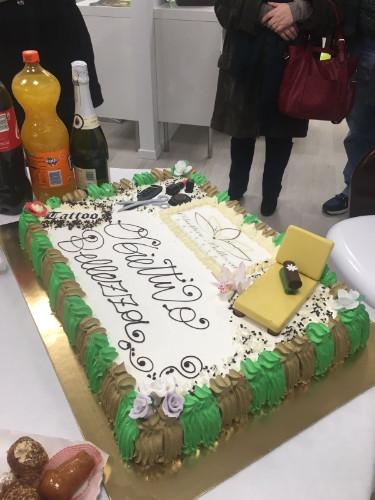 una grande torta alla panna bianca e ai bordi verde e marrone