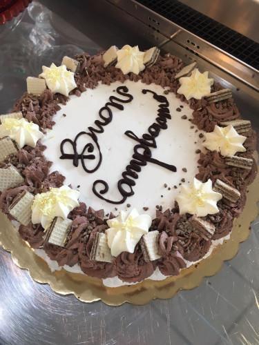 una torta di compleanno con panna, stelle di meringa, wafer e cioccolato
