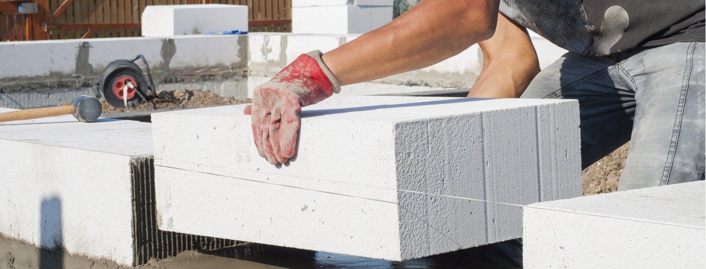 Un operaio mette in posa un blocco di cemento