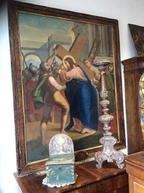 Tabella con motivo religioso dietro un mobile antico dove vi è una cassa e un candelabro anche vecchi