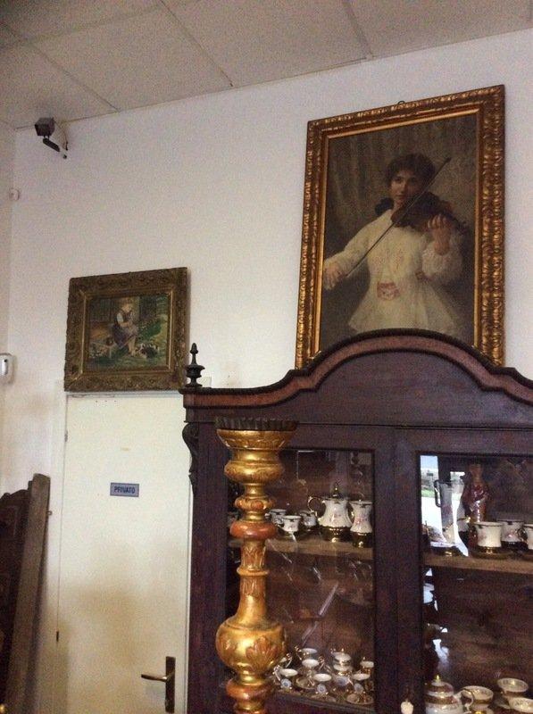 Ritratto di una dama di nero appoggiato su un vecchio specchio di quadro dorato, due grandi candelabri vecchi e tre piccoli vasi
