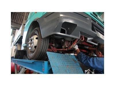 meccanico ripara la parte sotto di una macchina sollevata