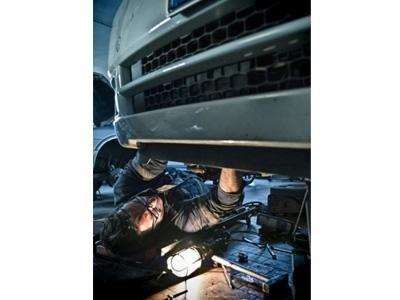 un meccanico sta riparando  una macchina sollevata