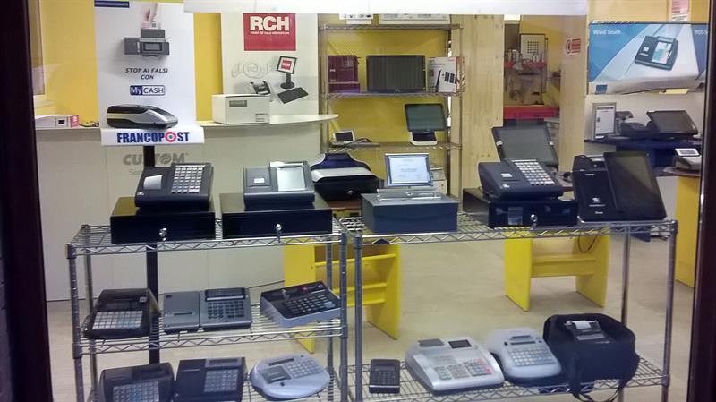 vista attraverso la vetrina di alcuni registratori di cassa esposti in un negozio