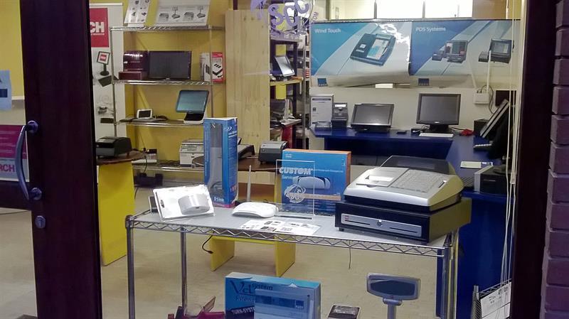 vista da lontano di tre vetrine di un negozio con scritto TECNO SYSTEM sas