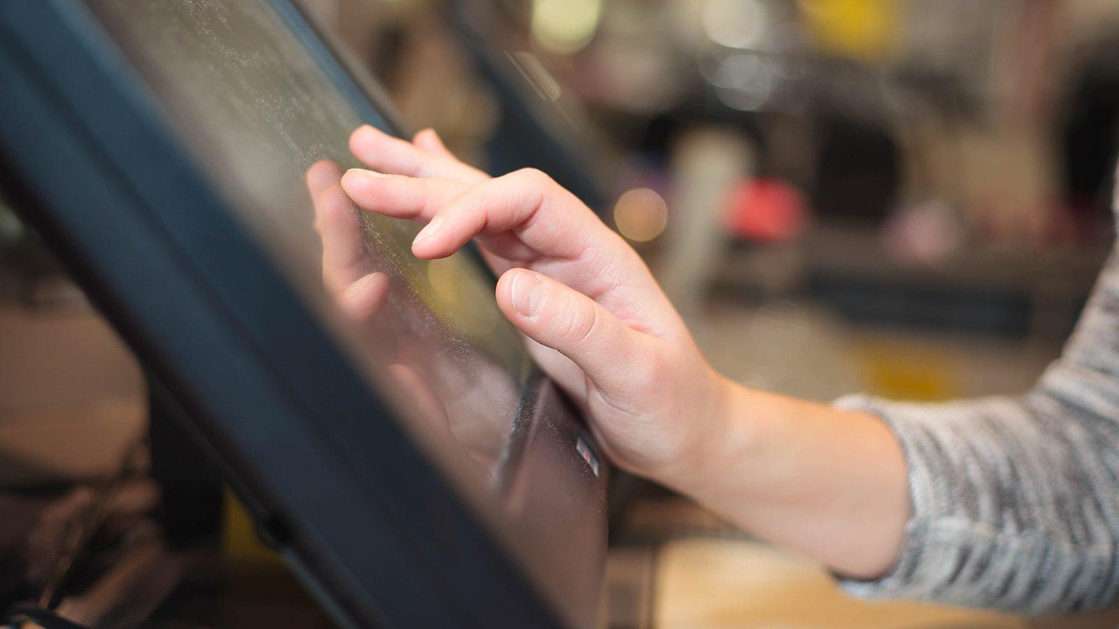 Una mano pigia dei tasti sul touch screen di un registratore di cassa