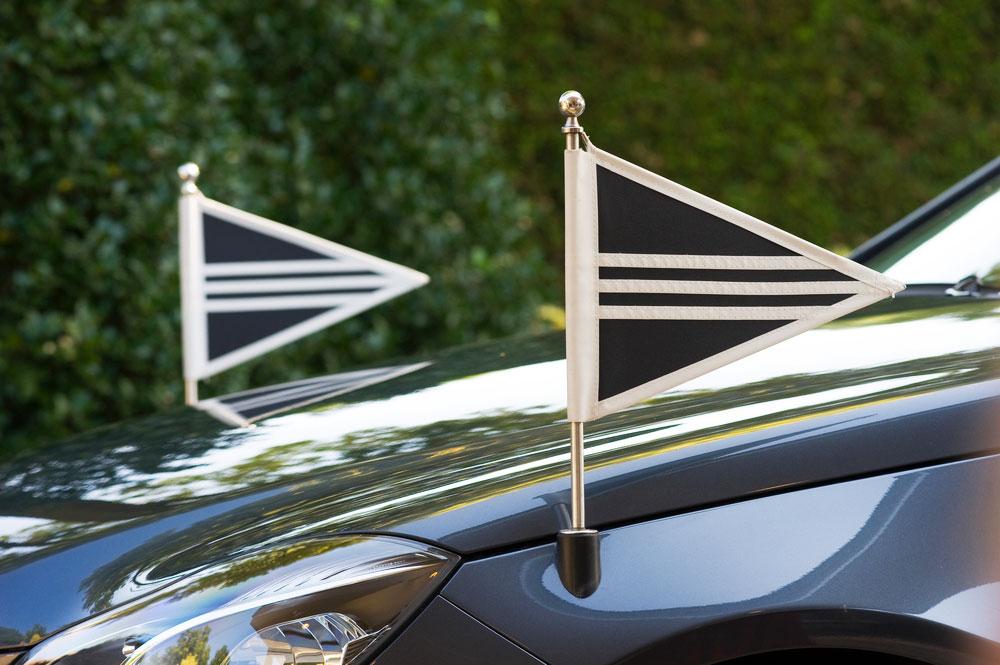 Due bandierine sulla parte anteriore di una vettura di lutto