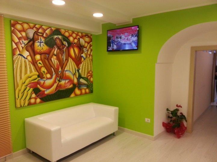 una sala da attesa con un divano di color bianco e un