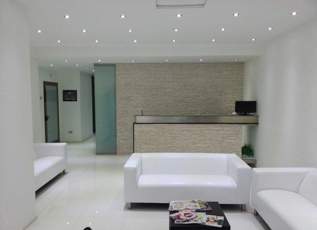una reception con un bancone e due divani bianchi