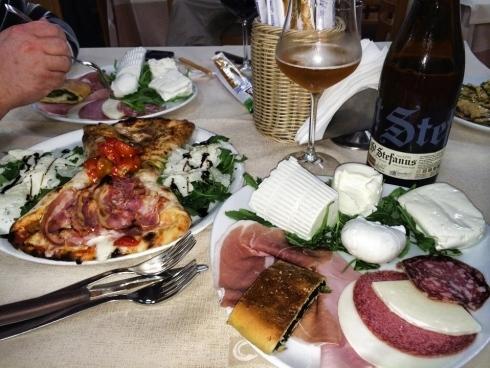tavolo con varie pietanze e calice di vino