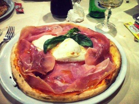 pizza con mozzarella di bufala e basilico in mezzo e prosciutto ai lati