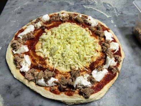 pizza cruda pronta da infornare con creazione di mozzarella e tonno