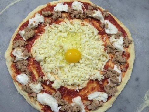 pizza con tonno mozzarella e uovo crudo in mezzo