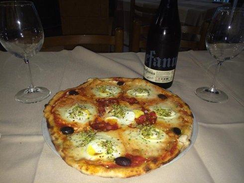 pizza margherita su un tavolo con accanto una bottiglia di vino