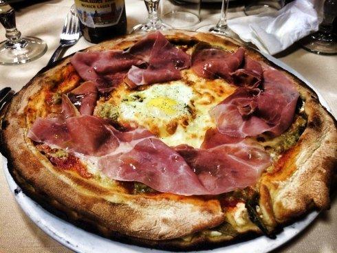 pizza con uovo strapazzato in mezzo e prosciutto crudo