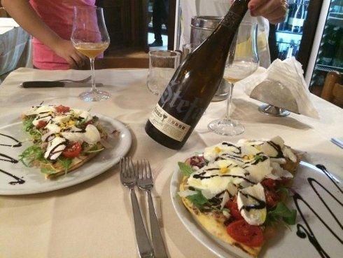 tavolo apparecchiato con secondi piatti e bottiglia di vino