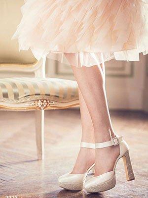 le gambe di una donna con le scarpe coi tacchi di color avorio