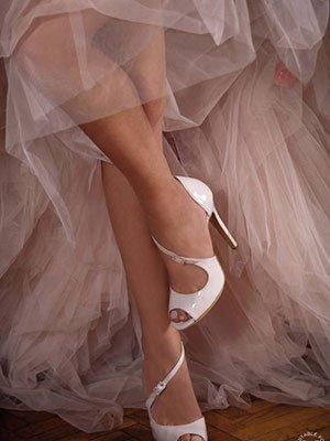 gambe di una donna con le scarpe coi tacchi di color bianco