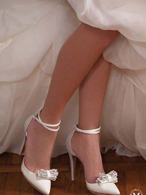 gambe di una donna con le  scarpe a tacchi di color avorio