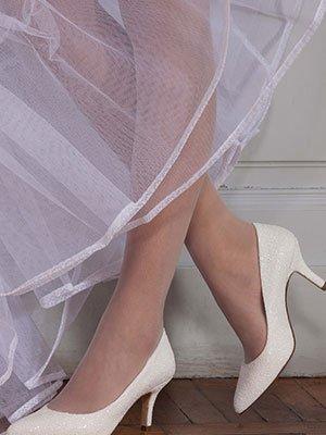 le gambe di una donna che indossa delle scarpe da cerimonia con i tacchi bianche