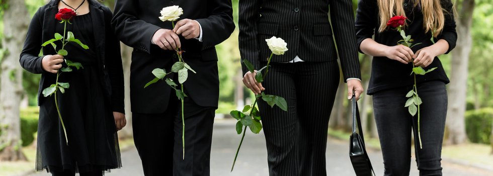 4 persone con vestiti scuri e dei fiori in mano