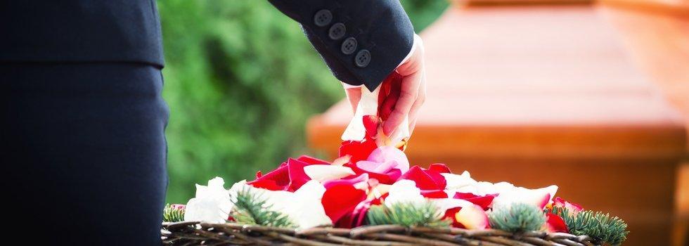 mano di un uomo che raccoglie dei petali da un cestino e sullo sfondo una bara sfocata
